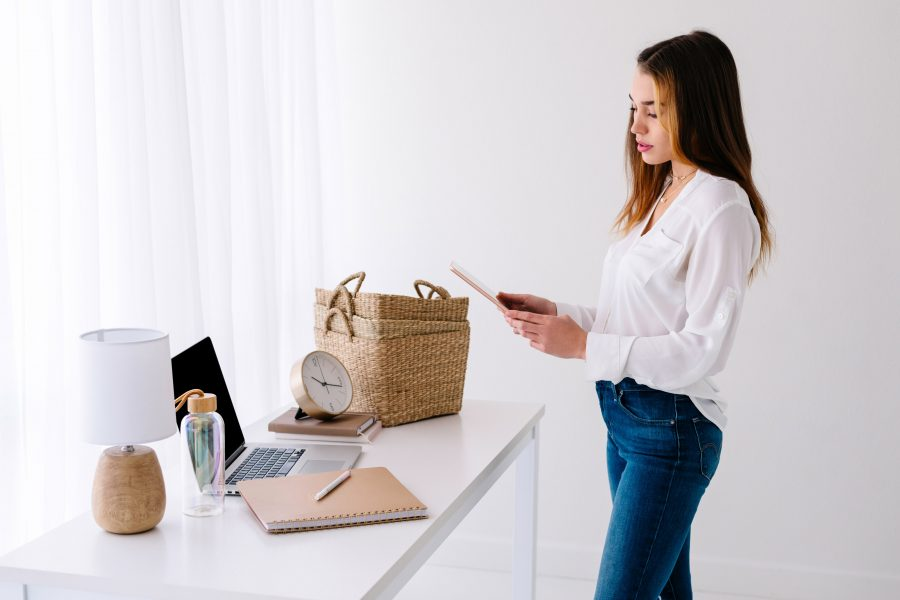 Image of a woman standing at her desk for the blog post Habits to Improve Your Life - Part Two