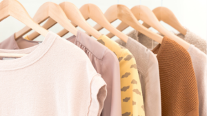 Image of clothes on hangars for the blog post How to Win at Decluttering