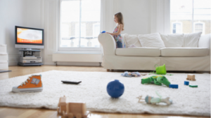 Image of a girl on a sofa with toys on the floor for the blog post How to Clear the Clutter and Restore Inner Calm
