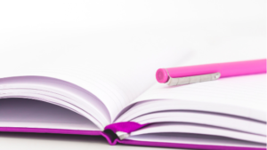Image of a pink notebook and pen for the blog post Why You Should be Setting Intentions as Well as Setting Goals