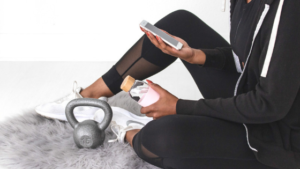 Image of a woman in her workout gear using her phone for the blog post Why You Should be Setting Intentions as Well as Setting Goals
