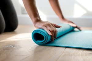 Image of a woman rolling up a yoga mat for the blog post How to Live Your Best Life