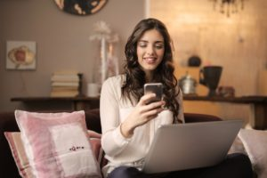 Image of a woman using her laptop and phone for the blog post How to Feel Like You Have it all Together...Even Though You Don't