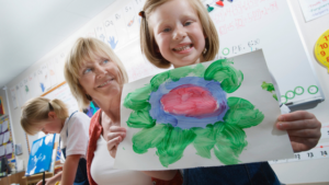 Image of a schoolgirl in class holding a painting for the blog post Back to School Goals for Students and Parents