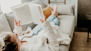 Image of a woman laying on the sofa reading for the blog post How to Easily Add a Self-Care Routine to Your Day