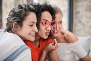 Image of three women using selfie props for the blog post The Self-Care Toolkit