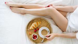 Image of a woman having breakfast on her bed for the blog post Self-Care isn't Selfish
