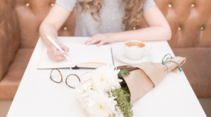 Image of a woman journaling at a table for the blog post How to Put Yourself First Every Single Day