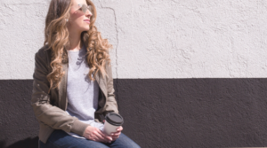 Image of a woman sitting on a bench with a cup of coffee for the blog post How to Put Yourself First Every Single Day