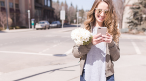 Image of a woman walking whilst texting on her phone for the blog post How to Put Yourself First Every Single Day
