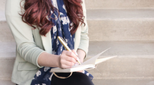 Image of a woman journaling for the blog post How to Put Yourself First Every Single Day