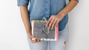 Image of a woman standing and holding two notebooks for the blog post My Year of 30-Day Challenges