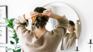 Image of a woman tying her hair in front of a mirror for the blog post Take control of your life with this week's favourite finds.