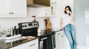 Image of a woman standing in her kitchen for the blog post What I Learned from my 30-Day Minimalism Challenge