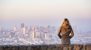 Image of a woman sitting on a wall looking at the view of a city for the blog post 100 self-reflection questions for personal growth