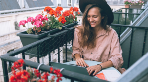 Image of a woman sitting on a balcony using her laptop for the blog post 100 self-reflection questions for personal growth