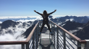Image of a woman admiring the view on the top of a mountain for the blog post 100 self-reflection questions for personal growth