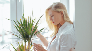 Image of a woman sitting next to a plant for the blog post Five simple ways to bring more gratitude to your day