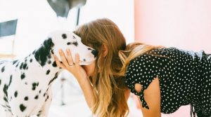 Image of a woman kneeling with her dalmation for the blog post Positive Affirmations for Self-Esteem