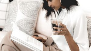 Image of a woman reading a magazine and holding a cup of coffee for the blog post Positive Affirmations for Self-Love