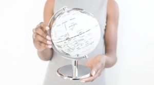 Image of a woman holding a globe for the blog post: How to Discover Your Life Purpose